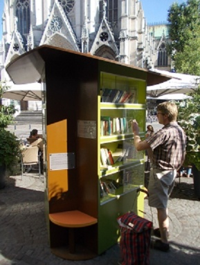 l'Arbre aux Livres, (Little Free Library) Nancy, France: volunteer restocking and tidying the collection